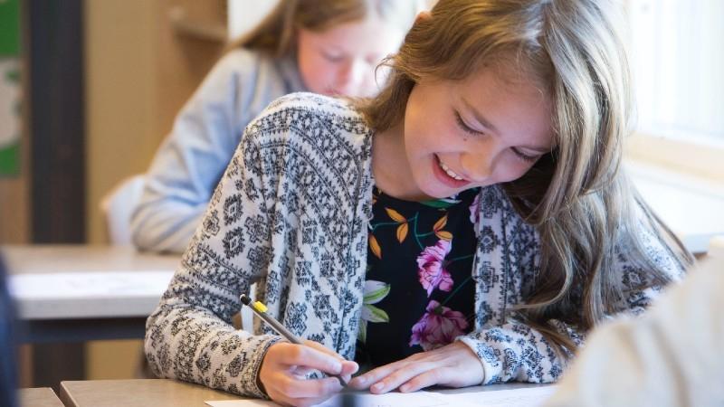 Ung flicka sitter vid skolbänk och skriver